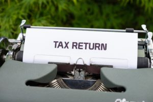 """Picture of a typewriter with the words """"tax returm"""""""